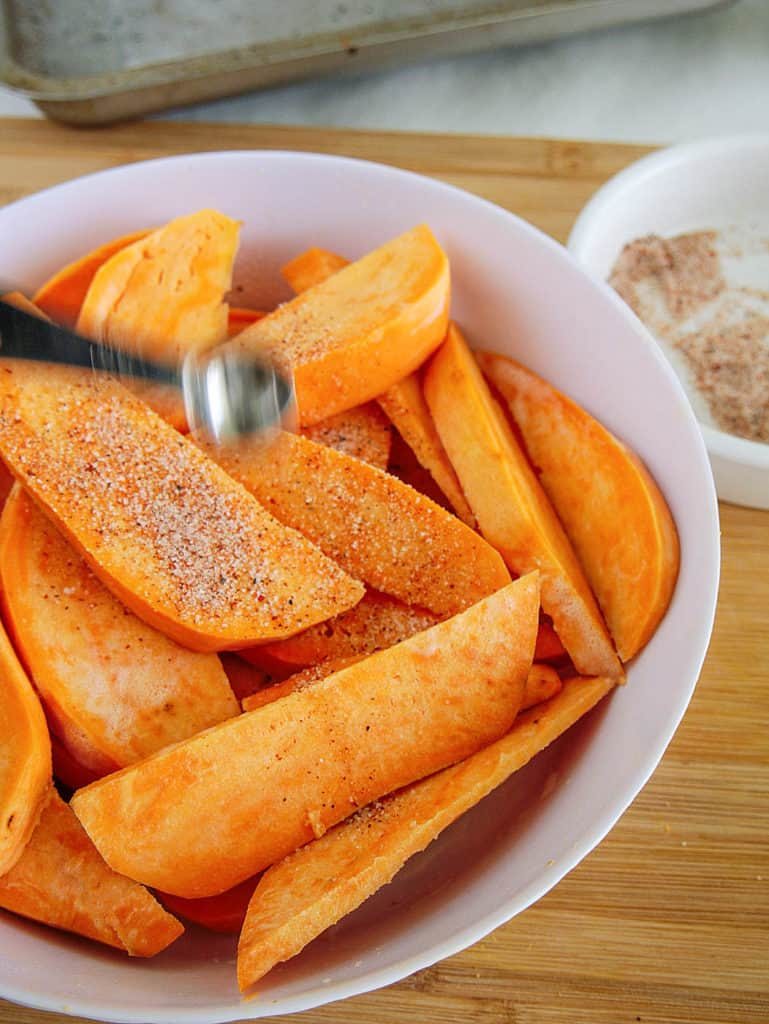 sweet potato slices being seasoned