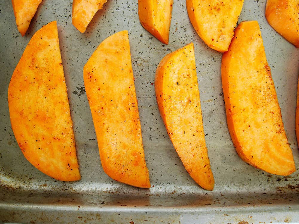 sliced sweet potato fries on a baking sheet