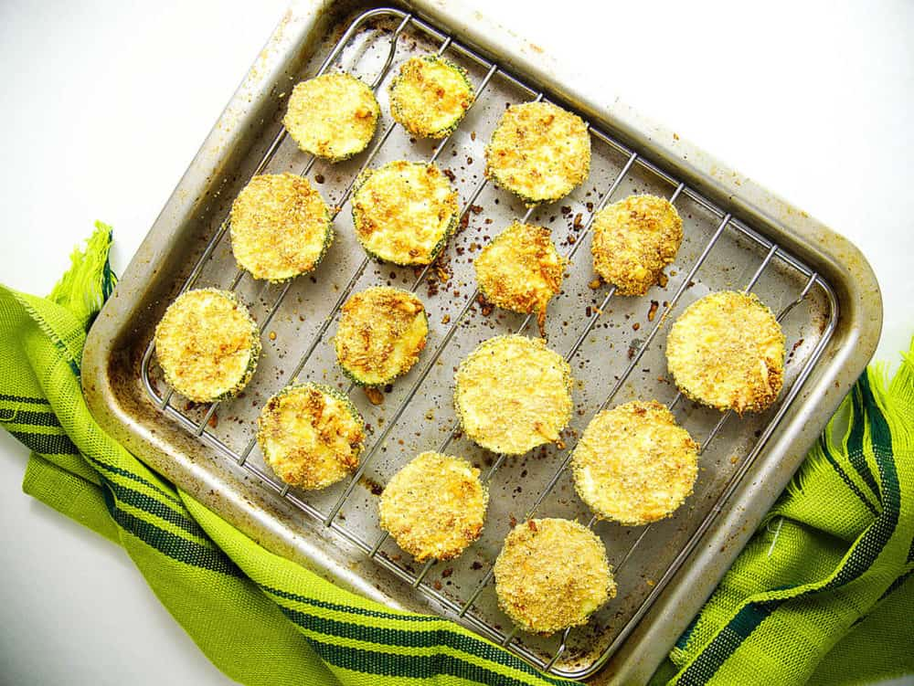 baked and crispy courgette chips with parmesan, fresh out of the oven on a tray