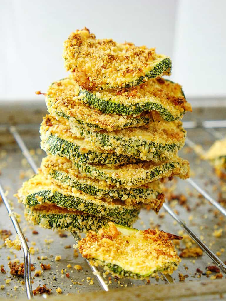 baked and crispy courgette chips with parmesan, stacked on an oven rack