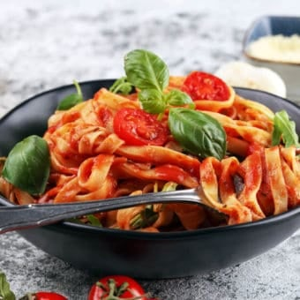Vegetarian Spaghetti Sauce with whole wheat pasta, served in a black bowl with basil on top