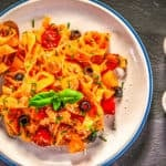 homemade tagliatelle with fresh tomatoes and parmesan on wood background