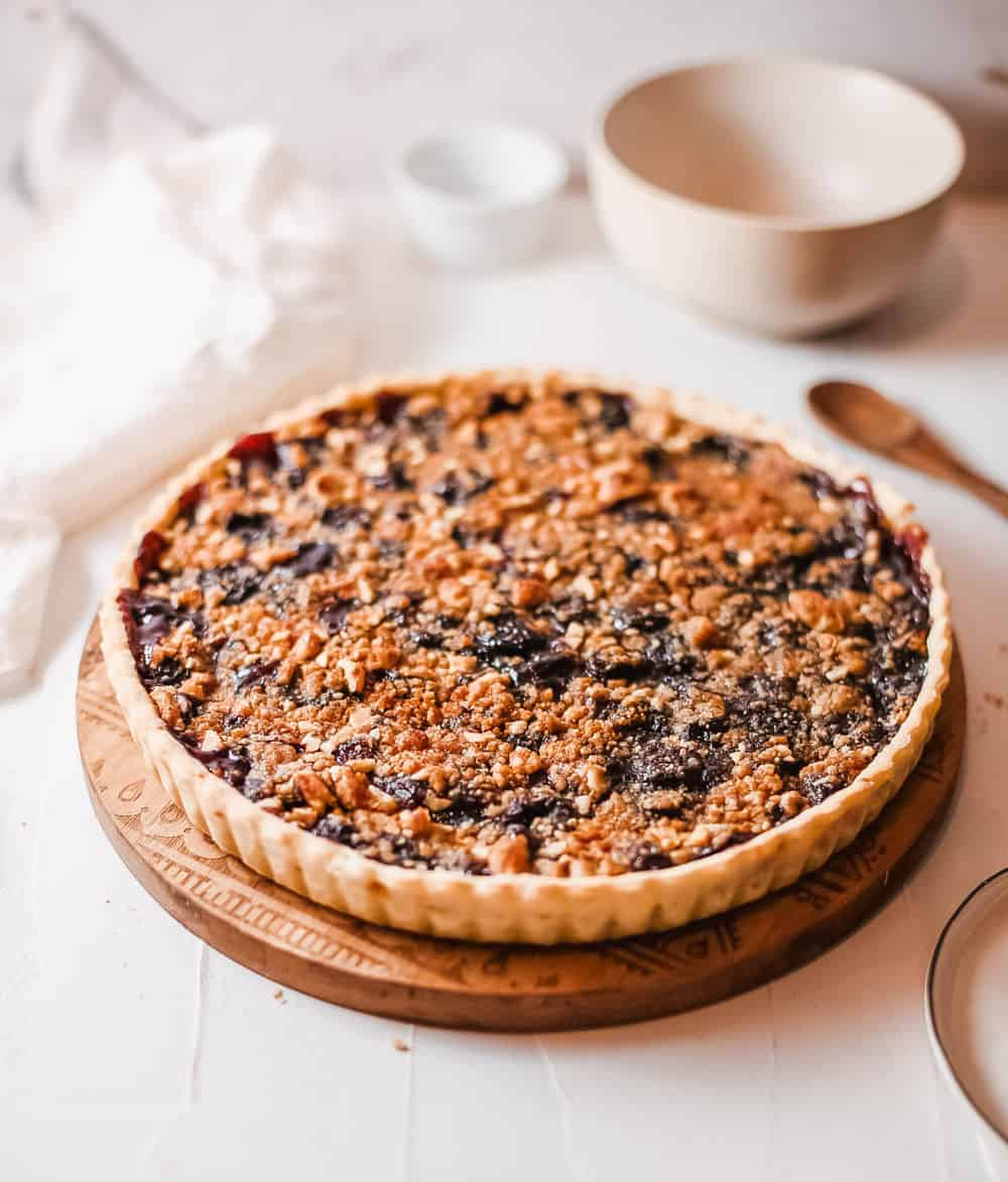 cherry crumb pie against a white background, side view