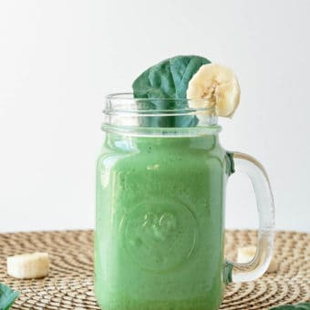 spinach banana smoothie with peanut butter served in a glass mason jar