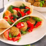 closeup of falafel wrap recipe with tomatoes, spinach and tahini sauce served on a white plate