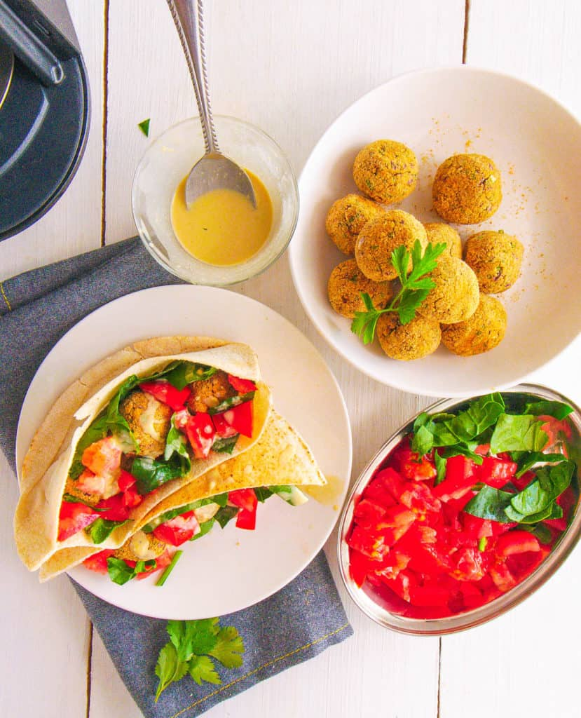 top view of falafel wrap recipe with tomatoes, spinach and tahini sauce served on a white plate with falafel balls and toppings