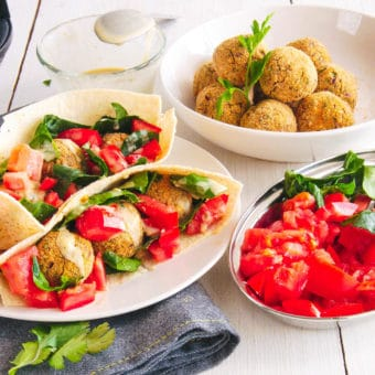 falafel wrap recipe with tomatoes, spinach and tahini sauce served on a white plate with falafel balls in the background
