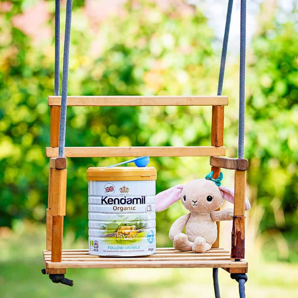 kendamil formula container stage 2 on a swing next to a stuffy