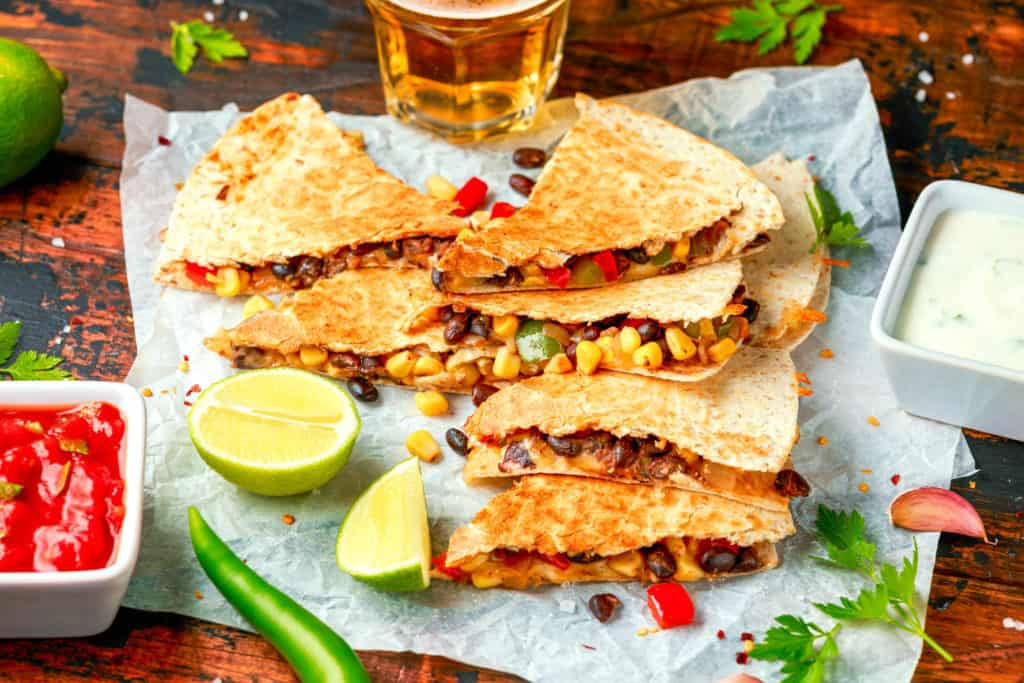 veggie quesadilla recipe - vegetarian mexican black beans tomato cheese and corn quesadilla served with cold beer salsa and yogurt dip sause on dark wooden background. healthy food