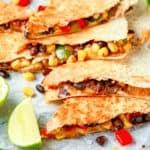 veggie quesadilla recipe - vegetarian black beans tomato corn quesadilla served with cold beer salsa and yogurt dip sause on dark wooden background.