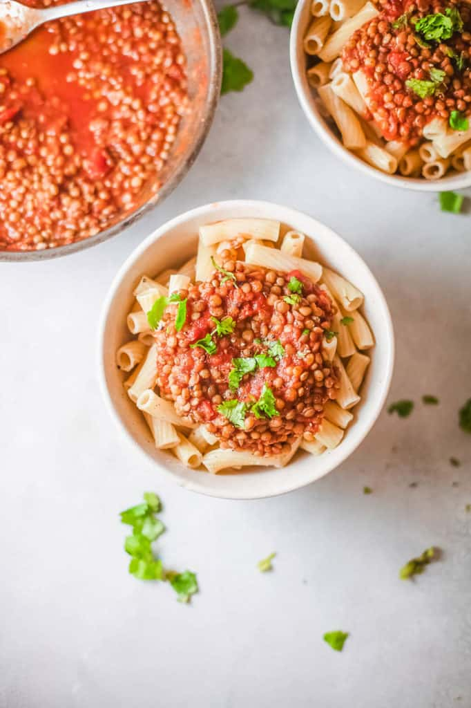 vegan bolognese with lentils, served over pasta in a white bowl