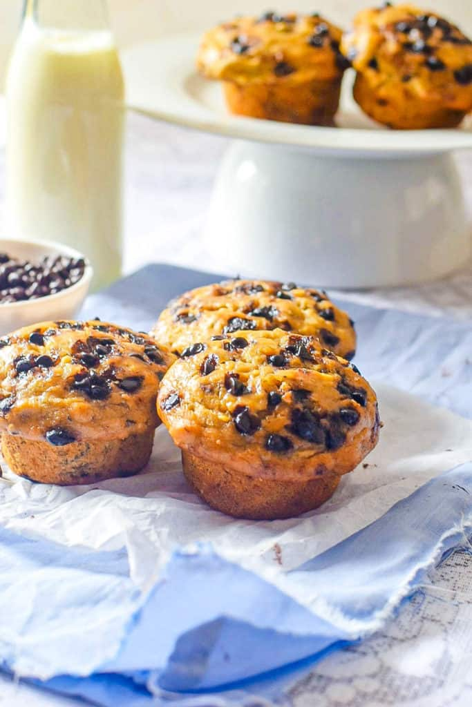 Chocolate Banana Muffin on a blue napkin with milk and muffins in the background