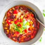 The Best Instant Pot Vegetarian Chili served in a white bowl topped with green onions and cheese