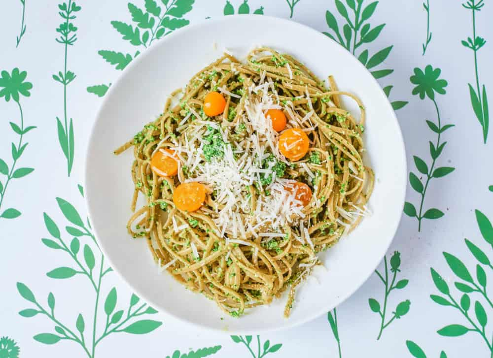vegetarian pesto pasta with spinach and herbs, served on a white plate