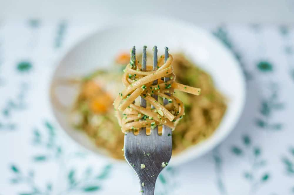 fork of vegetarian pesto pasta with spinach and herbs, served on a white plate