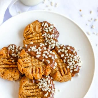 Keto Peanut Butter Cookies dipped in chocolate and nuts, on white plate