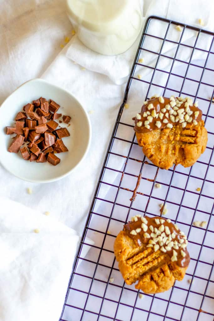 Keto Peanut Butter Cookies dipped in chocolate and nuts, on wire rack