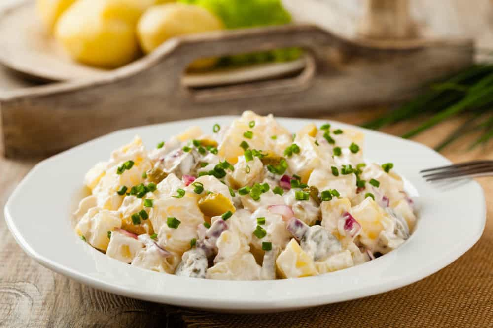 The Perfect Healthy Potato Salad in a white bowl topped with sliced green onions