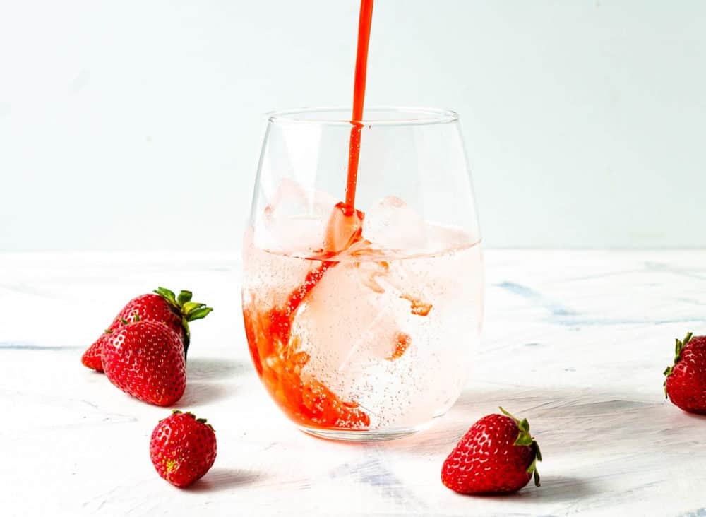 strawberry soda made with Strawberry Simple Syrup in a glass with ice