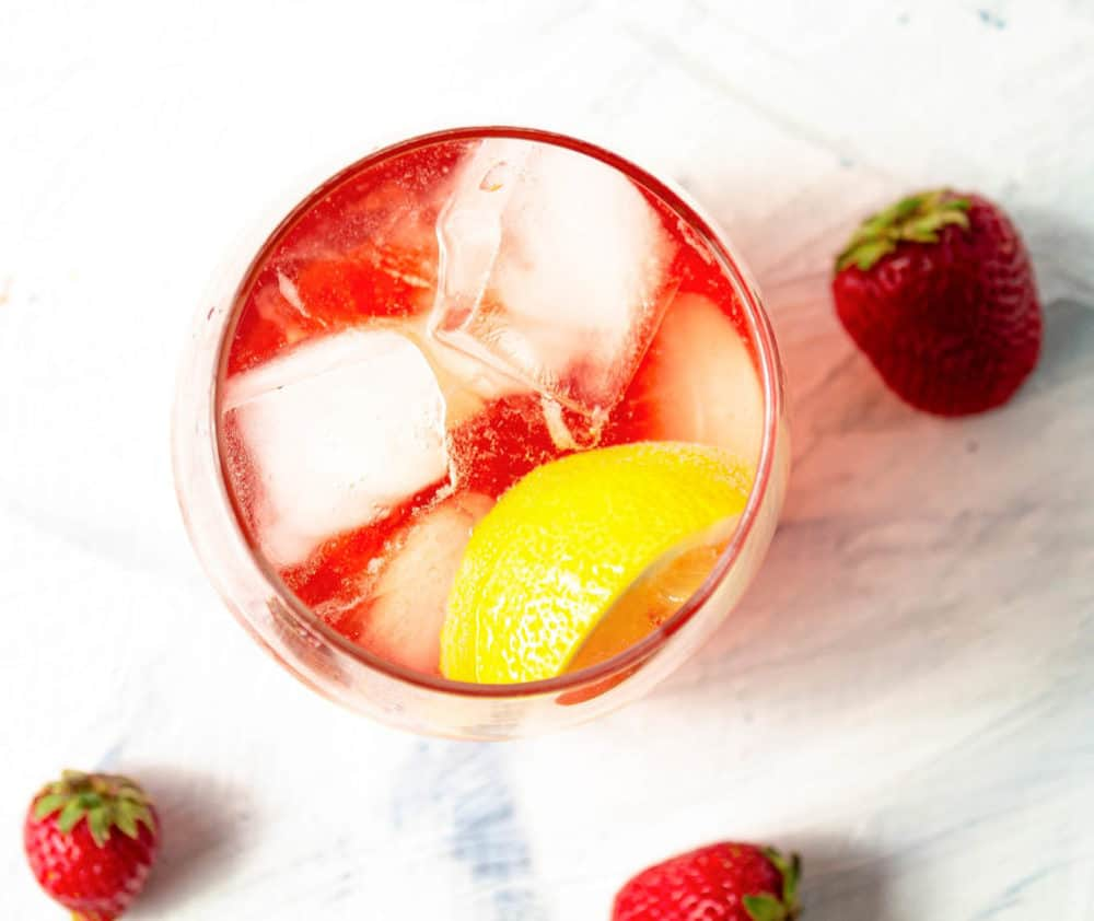 top view of strawberry soda made with Strawberry Simple Syrup in a glass with ice and lemon