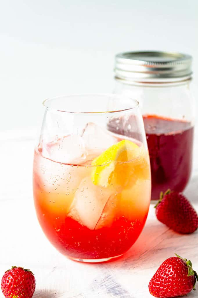 strawberry soda made with Strawberry Simple Syrup in a glass with ice and lemon