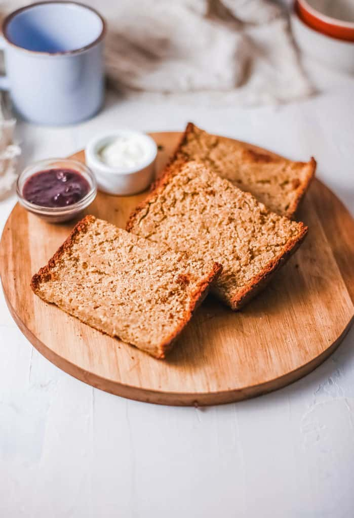 gluten free bread served on a wooden board with a side of jam and butter