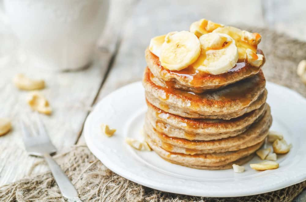 Healthy Pancakes Made with Oats and Sprouted Wheat topped with bananas and served on a white plate