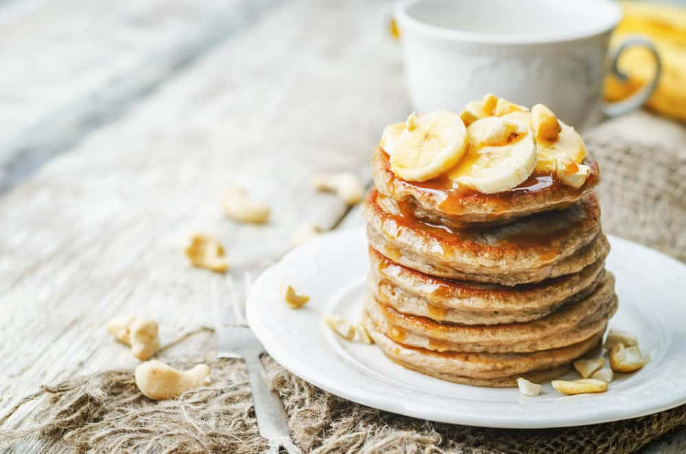 Pancakes Made with Oats and Sprouted Wheat topped with bananas and served on a white plate