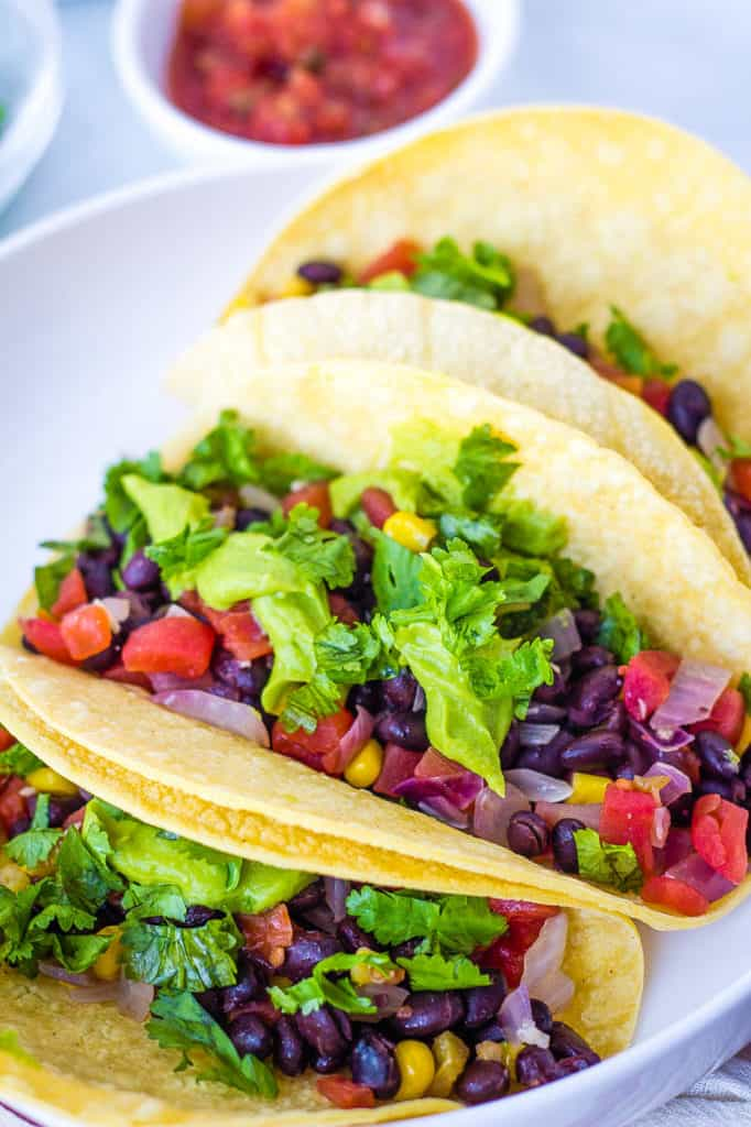 vegan tacos with black beans, avocado, veggies, and cilantro, served on a white plate - vegetarian gluten free recipes