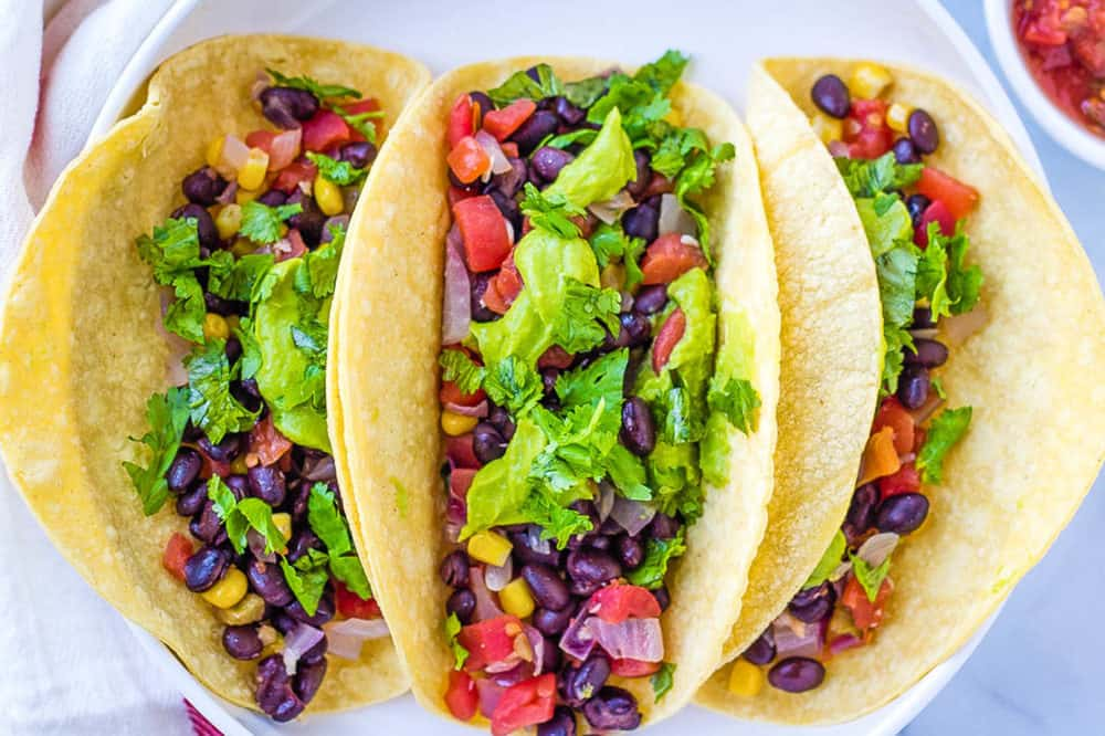 vegan tacos with black beans, avocado, veggies, and cilantro, served on a white plate