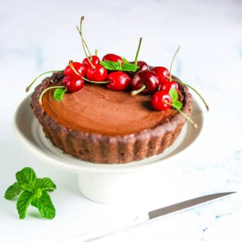 Chocolate Ganache Tart with cherries on top, served on a white plate