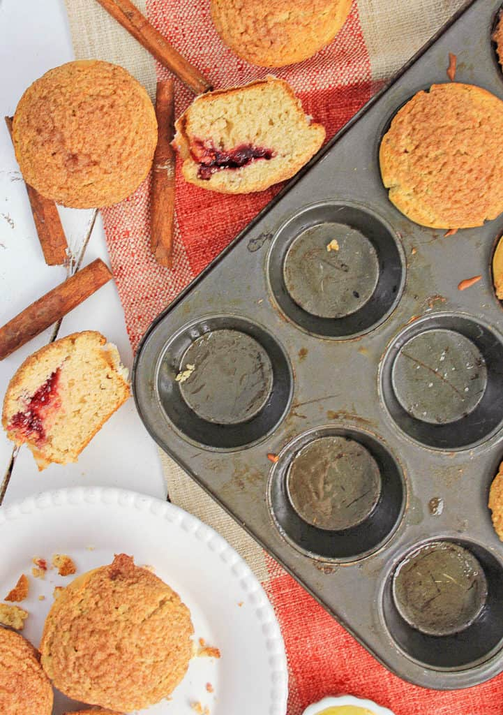 cinnamon muffins pictured both in a muffin tin and cut in half on a tray