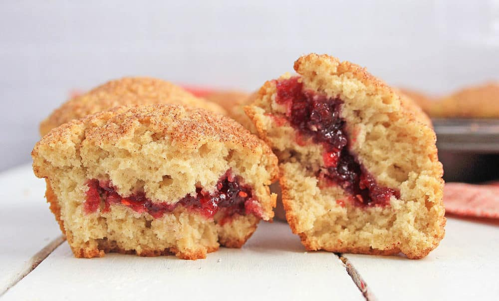 cinnamon muffins cut in half with the raspberry jelly filling pictured