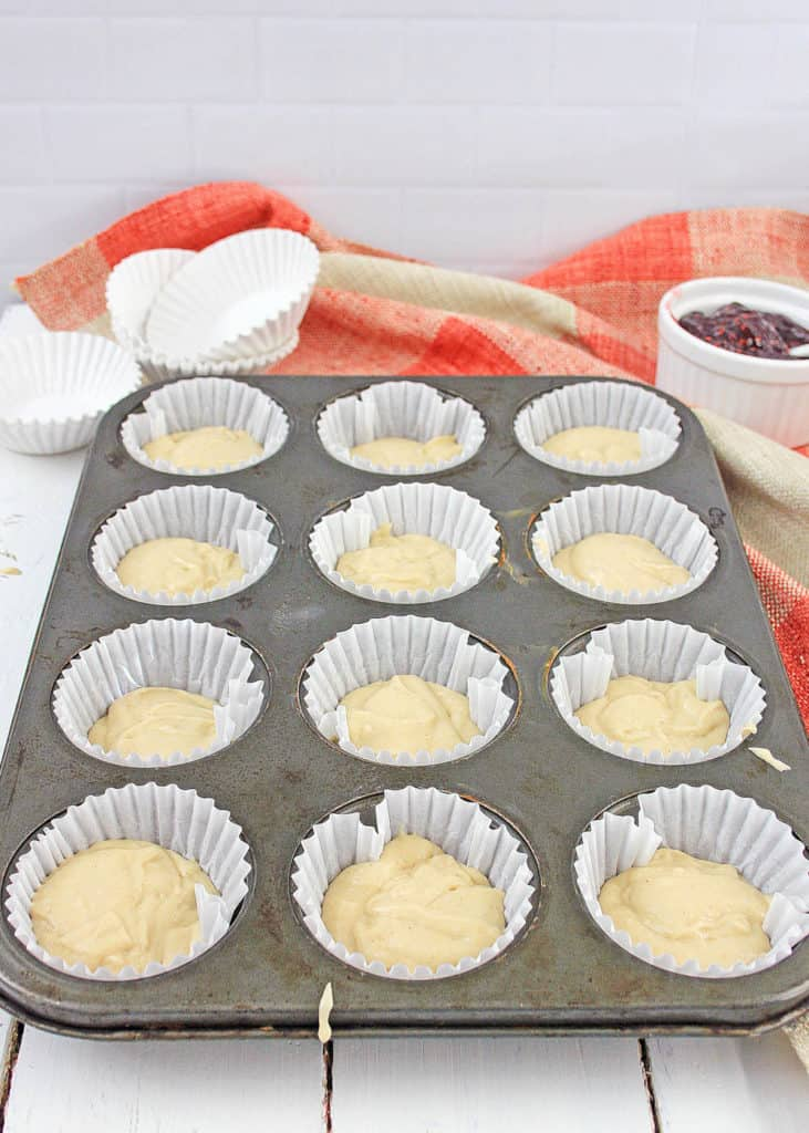 batter in cupckae liners in a muffin tin