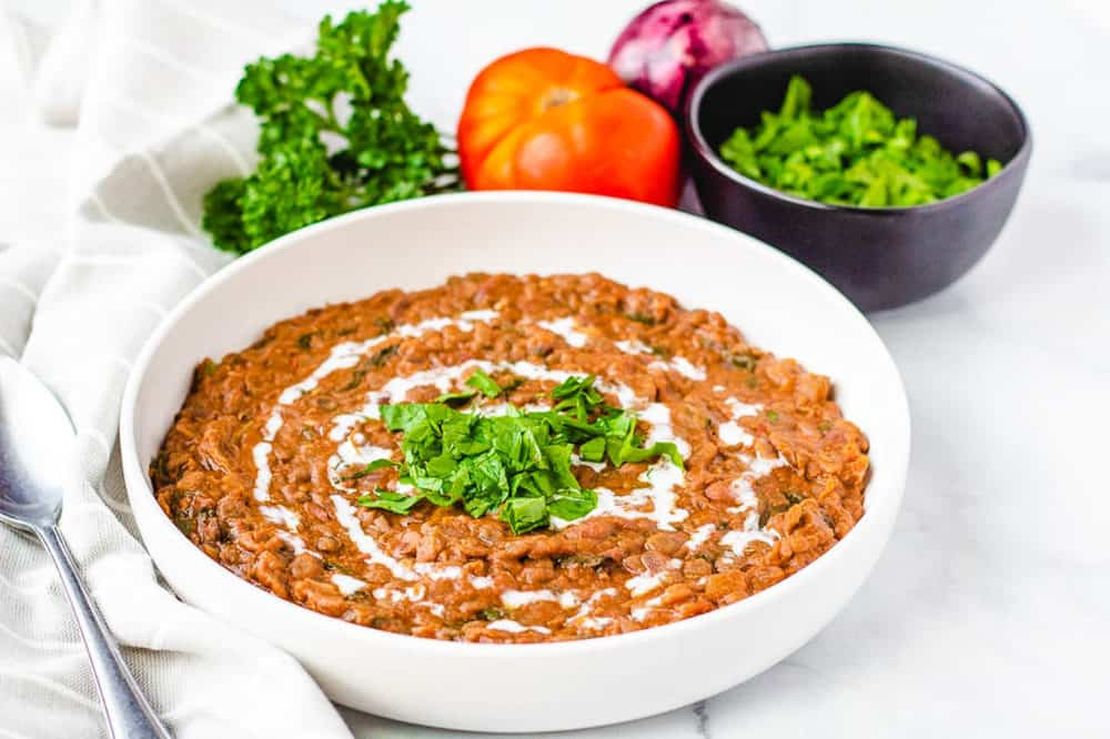 side view of instant pot vegan dal makhani recipe, served in a white bowl with fresh herbs on top