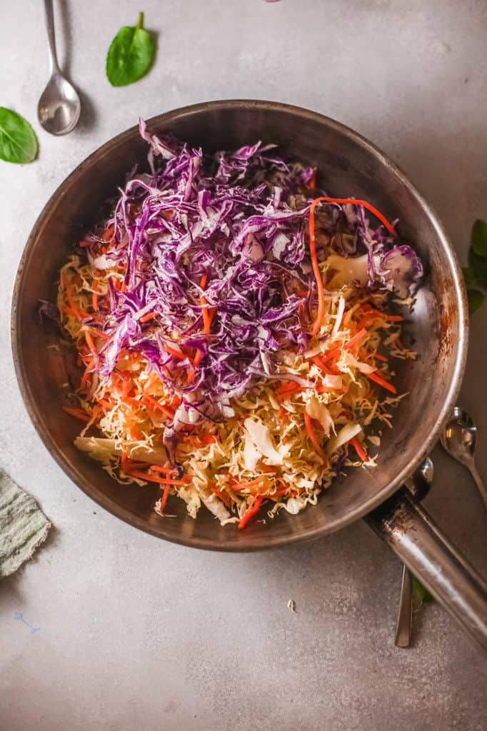 cabbage and carrots sauteeing in a pan