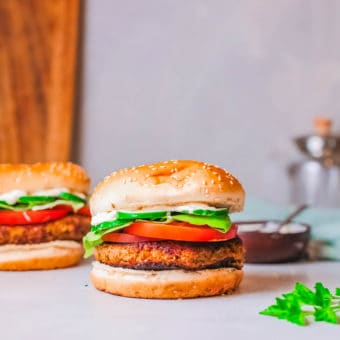 falafel burgers pictured against a marble background, topped with tomatoes and lettuce and a feta sauce
