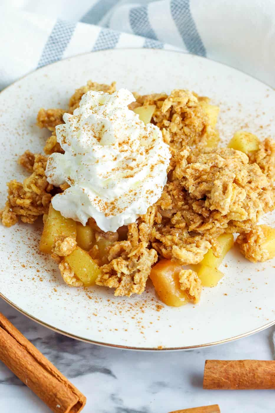 gluten free apple crisp served on a white plate topped with whipped cream