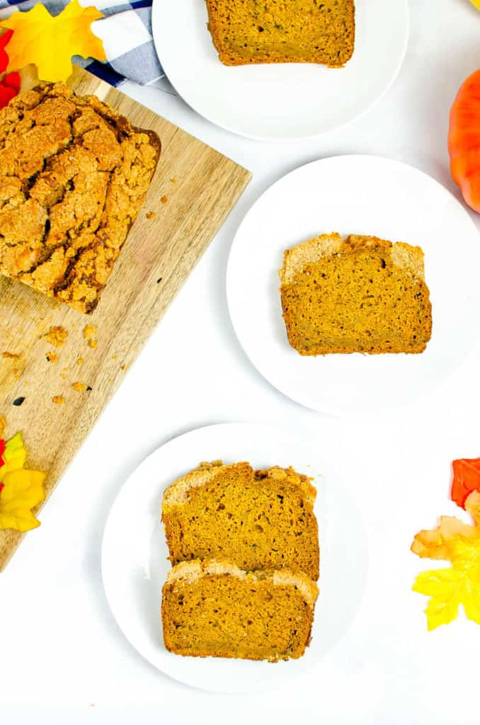 slices of gluten free coffee cake with pumpkin on a white plate with full bread loaf in the corner