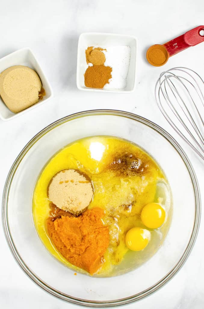 bananas, pumpkin, eggs, spices mixed together in a bowl