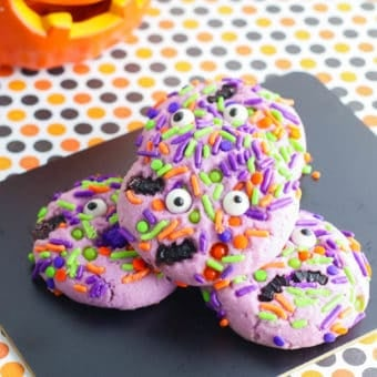 purple halloween monster cookies with googley eyes stacked on a black cutting board