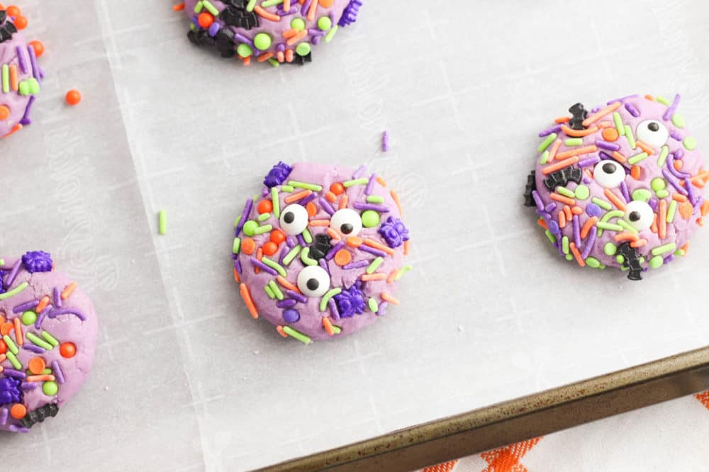 eyes added to purple cookie dough balls on a baking sheet lined with parchment paper