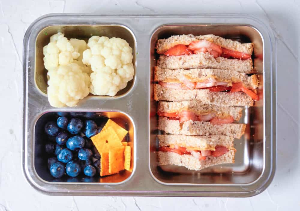 Healthy Lunch Ideas for Toddlers - sprouted wheat sandwich with peanut butter, strawberries, blueberries, crackers, cauliflower