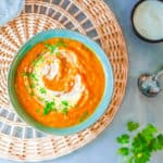 pumpkin and sweet potato soup, served in a blue bowl, topped with fresh herbs and coconut cream