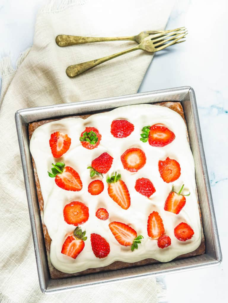three milk cake topped with whipped cream frosting and strawberries in a square pan