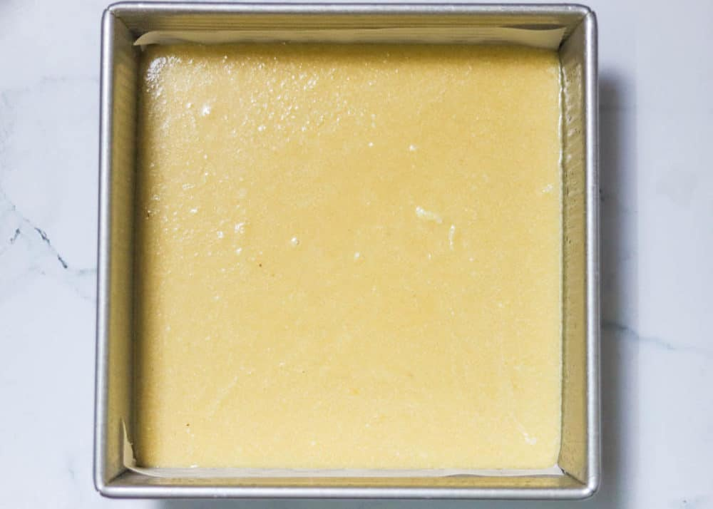 milk cake being poured into a square pan