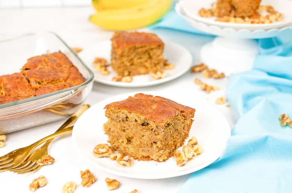 vegan banana bread, served on a white plate with a blue napkin in the background