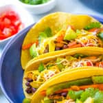 vegetarian fajitas in a corn tortilla topped with cheese, avocado and cilantro, served in a blue bowl