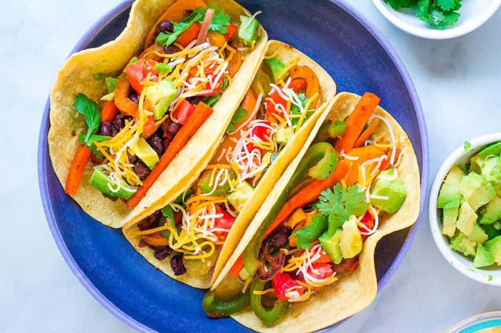 top view of vegetarian fajitas in a corn tortilla topped with cheese, avocado and cilantro, served in a blue bowl
