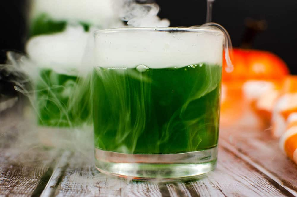 finished shot of green witches brew cocktail served in a square glass